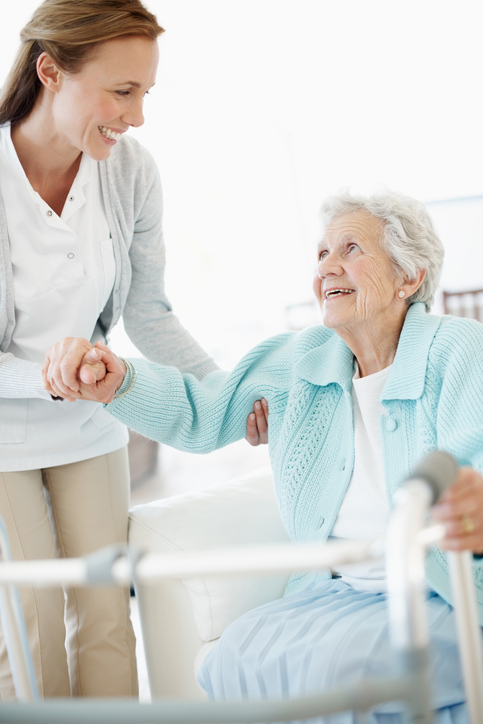 Daughter helping her elderly mother stand up in preparation to use her walker